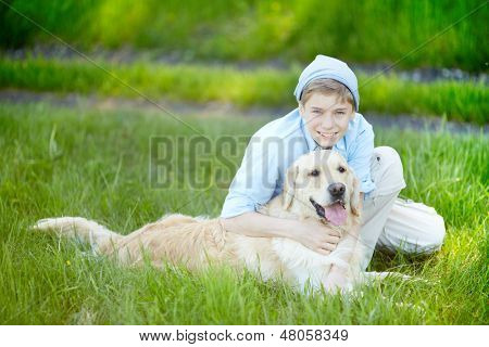 Portrait of cute lad embracing his fluffy friend and both looking at camera