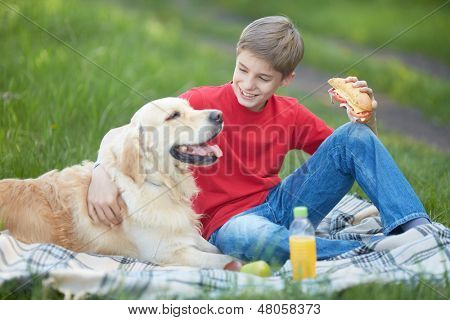 Portrait of cute lad and his fluffy friend having picnic