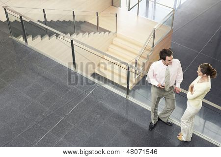 High angle view of business colleagues conversing while standing by railing in office