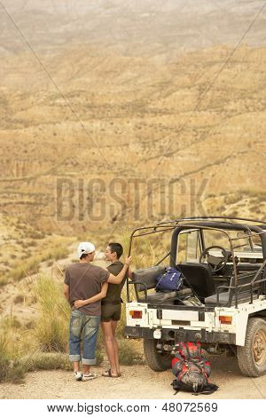 Rear view of affectionate couple looking at desert from cliff standing by four-wheel-drive car