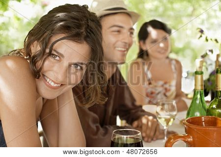Portrait of beautiful young woman with friends enjoying drinks at party