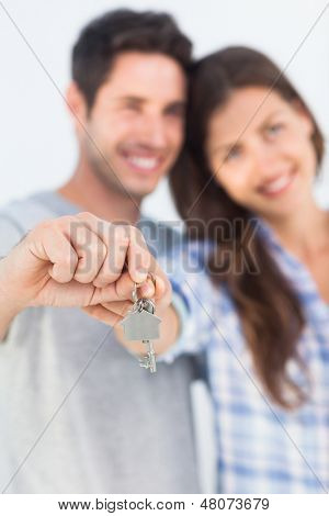 Cheerful man and wife presenting a key with a house keychain