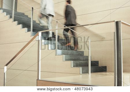 Blurred motion of businessmen moving up stairs in office