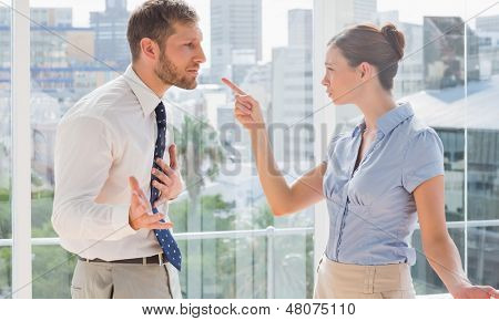 Business partners having a heated argument by large windows