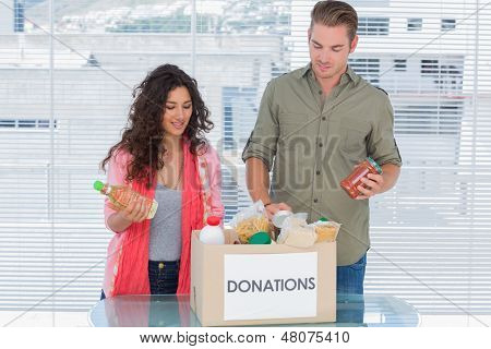 Volunteers taking out food from donations box for a charity