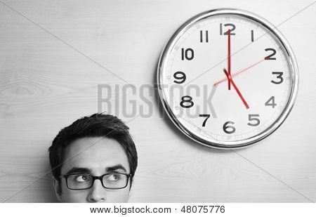 Headshot young businessman looking at clock on wall in office
