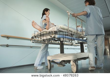 Low angle view of two nurses moving patient on gurney in hospital corridor