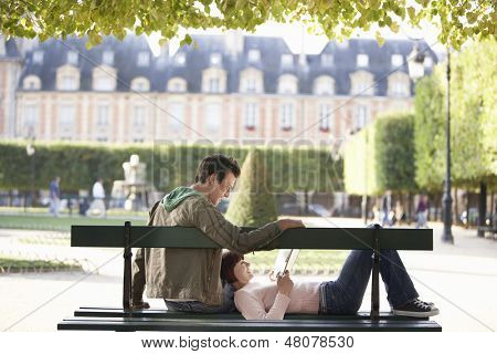 Relaxed young couple reading book on city park bench