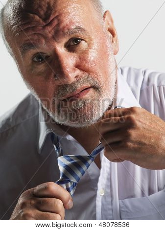 Closeup of a sweaty middle aged businessman loosening tie against white background