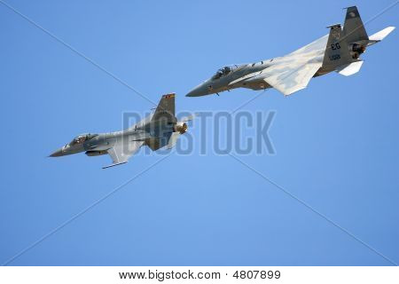 A F16 Fighting Falcon And An F15 Strike Eagle Fly Past In Formation