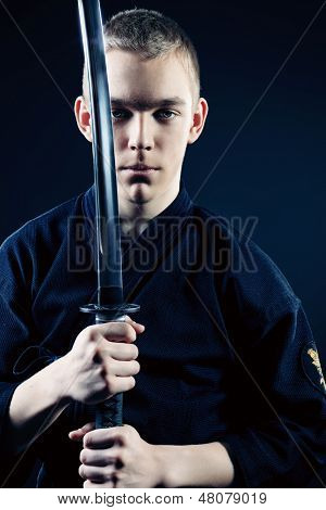 Handsome young man practicing kendo. Over dark background.