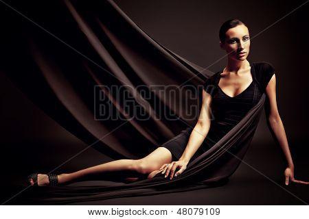 Kunst-Mode-Foto einer schönen Frau im schwarzen Kleid. Gegenüber dem schwarzen Hintergrund.
