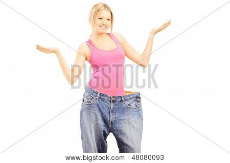 Happy weightless female with old pair of jeans gesturing with her hands, isolated on white background