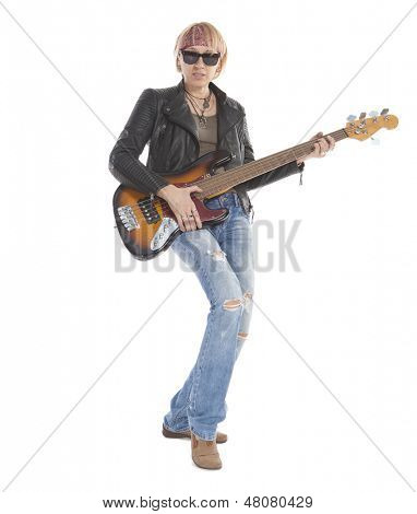 Woman with long legs playing guitar, wearing torn blue jeans and sunglasses, standing, looking at camera. Isolated on white