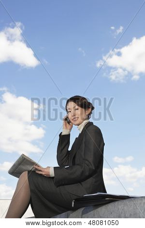 Low angle view of a young businesswoman using cellphone with newspaper against sky
