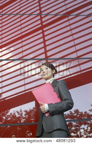 Low angle view of a confident businesswoman holding folder