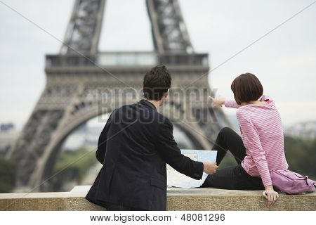 Rear view of a couple with map in front of Eiffel Tower