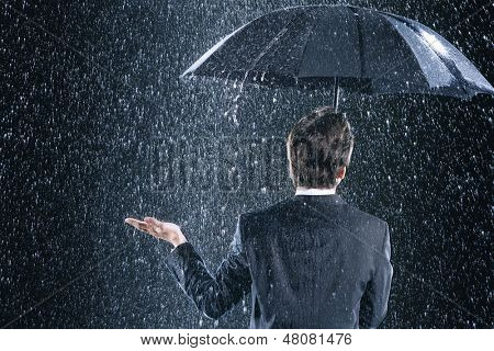 Rear view of a businessman staying dry under umbrella during downpour
