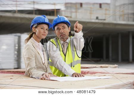 Architect and construction manager discussing plans at site