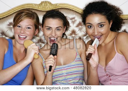 Portrait of teenage girls using brushes as microphones and singing at slumber party