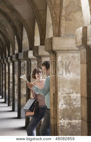 Happy young couple with shopping bags looking at map under archway