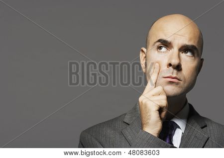 Closeup of a bald businessman with hand on cheek thinking against gray background