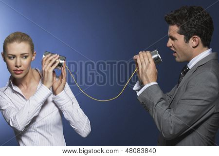 Businessman yelling at female colleague through tin can phone against blue background