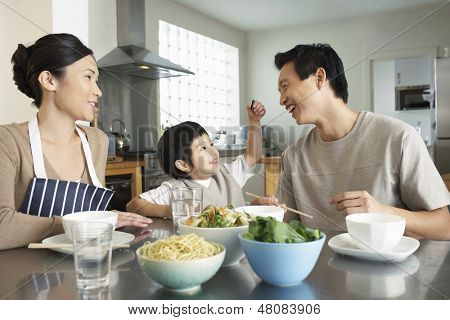 Happy young family enjoying meal at the kitchen table in house