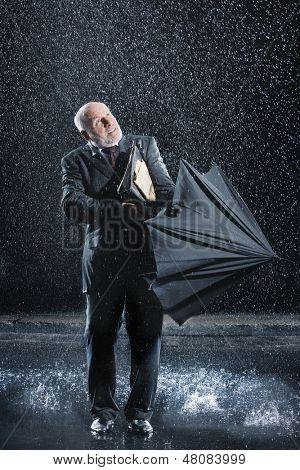 Medio de años luchando para abrir el paraguas durante lluvia repentina de empresario