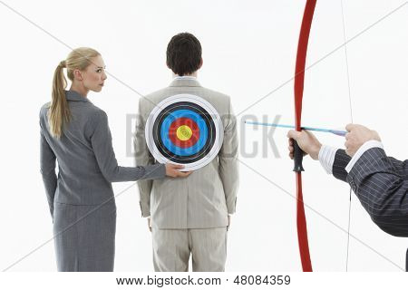 Business woman holding target to man's back while other man aims bow and arrow