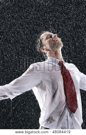 Businessman standing with arms outstretched and eyes closed in the rain