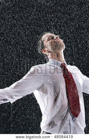 Empresario de pie con los brazos extendidos y los ojos cerrados bajo la lluvia