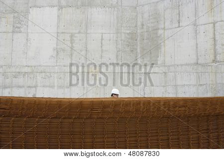 Side view of a man using cellphone behind stack of rebar at building site
