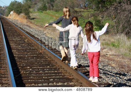 Girls Walking On Railroad Tracks