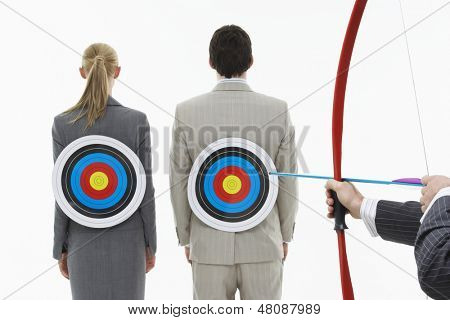 Rear view of two businesspeople with targets on backs while man aims bow and arrow