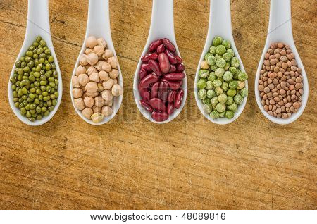 Various legumes on porcelain spoons on a wooden background