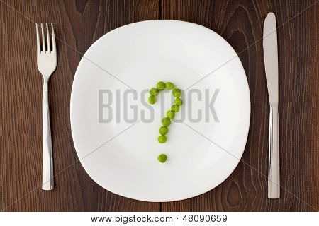 Question mark made of peas on plate