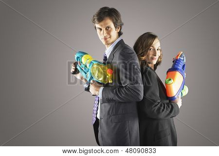 Side view of two smiling businesspeople standing back to back with water guns against gray background