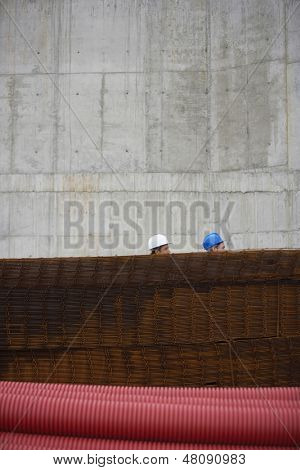 Side view of two construction workers behind a stack of rebar