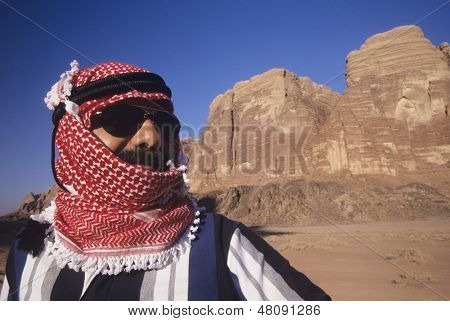 Closeup of an Arab man in turban wearing Sunglasses in desert landscape