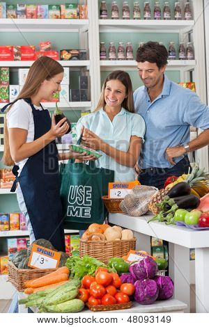 Young saleswoman showing vegetable packet to couple in supermarket