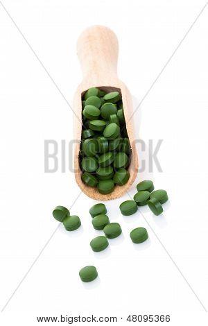Verdes pastillas a la cuchara de madera aisladas.