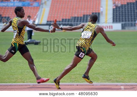 DONETSK, UKRAINE - JULY 13: Devaughn Baker pass the baton to Martin Manley, Jamaica, in the boys medley relay during World Youth Championships in Donetsk, Ukraine on July 13, 2013