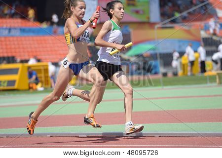 DONETSK, UKRAINE - JULY 13: Elena Strutinschi, Romania (left), and Sabrina Hocine, Algeria, compete in the medley relay during World Youth Championships in Donetsk, Ukraine on July 13, 2013