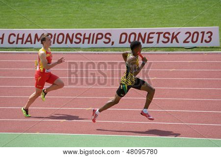 DONETSK, UKRAINE - JULY 13: Jaheel Hyde of Jamaica and Javier Delgado of Spain compete in the boys medley relay during World Youth Championships in Donetsk, Ukraine on July 13, 2013
