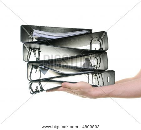 Hands Passing A Pile Of Ring Binders