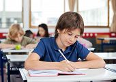 foto of schoolboys  - Little schoolboy writing in book at desk with classmates in background - JPG