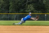stock photo of infield  - A young male plays baseball on a summer day - JPG