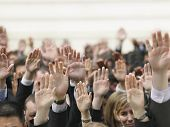 stock photo of democracy  - Closeup of business crowd raising hands - JPG