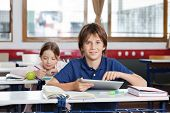 pic of schoolgirl  - Portrait of cute schoolboy using digital tablet with schoolgirl in background at classroom - JPG